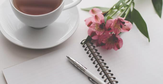 Whats the Difference Between a Ghostwriter and a Content Writer blog title overlay notebook and tea cup on a desk