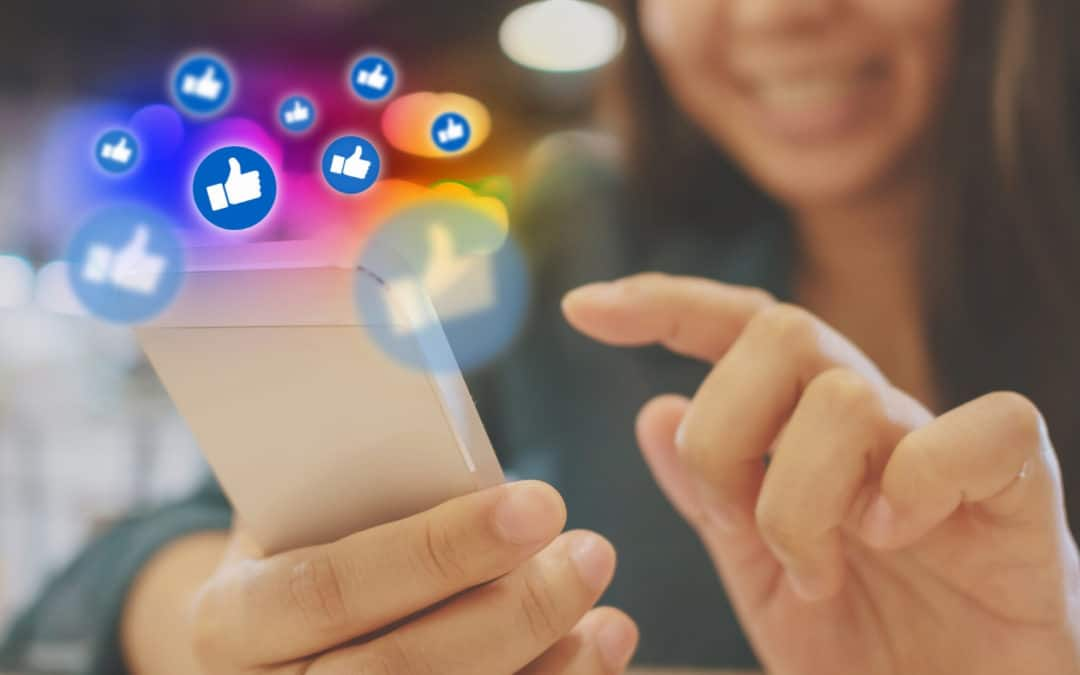 "Not your Typical ""What not to do on Social Media"" Post blog featured image girl smiling at her smartphone with social ""like"" icons floating away"
